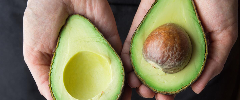 Avocado cut in half in hand